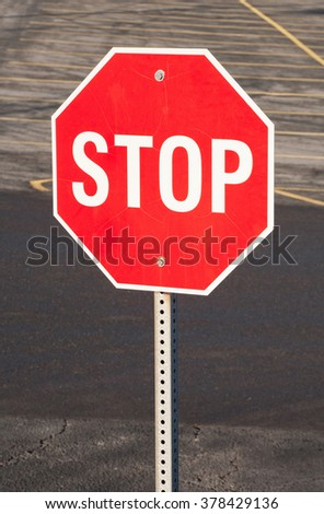Stop sign with parking lot in background.