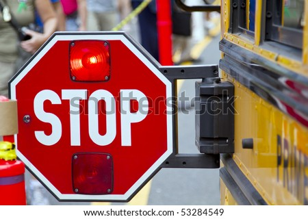 Stop sign with the flashing red light on the school bus.