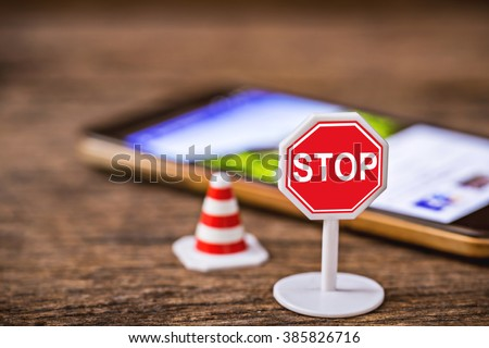 stop sign with traffic cone over blurred smart phone, tablet,cellphone on wooden floor,abstract background to safety drive don't use smartphone,cellphone or tablet concept. - stock photo