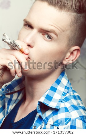 Stop Smoking Concept. Emotive portrait of a young fashionable hipster smoking too many cigarettes over vintage background. Trendy casual clothes. Close up. Studio shot