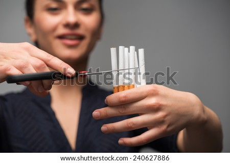 Stop smoking concept. Young beautiful woman cut cigarettes with scissors smiling, isolated on grey background, selective focus on hand - stock photo