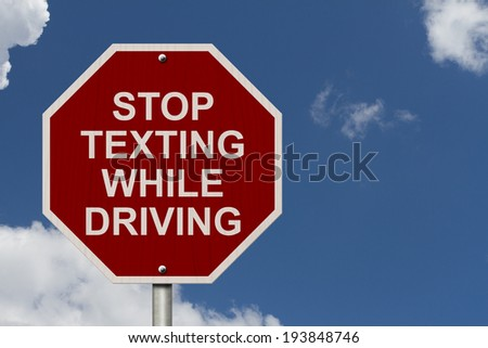 Stop Texting While Driving Sign, Red and White Stop sign with words Stop Texting While Driving with a blue sky background - stock photo
