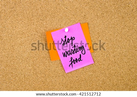 Stop Wasting Food written on paper note pinned on cork board with white thumbtack, copy space available - stock photo