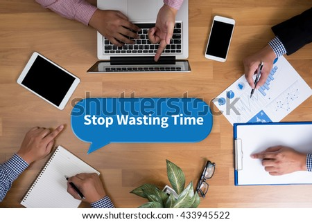 Stop Wasting Time Business team hands at work with financial reports and a laptop, top view - stock photo