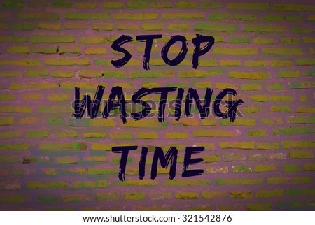 Stop wasting time message written on brick wall - stock photo
