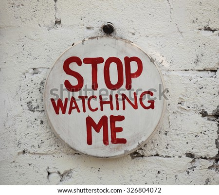Stop Watching Me sign hanging on wall - stock photo
