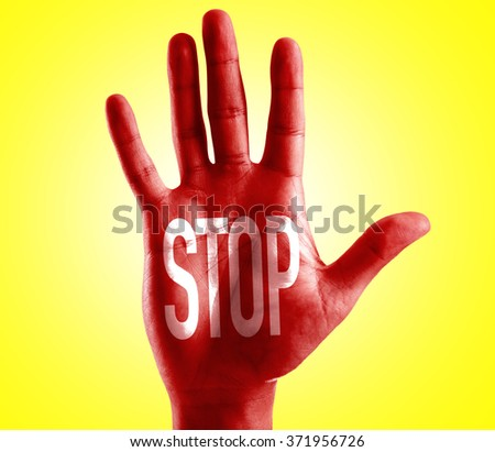 STOP written on hand with yellow background - stock photo