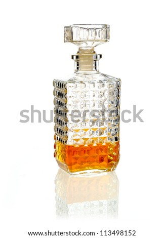 Stoppered whiskey or brandy decanter one third full of alcohol on a reflective white surface - stock photo