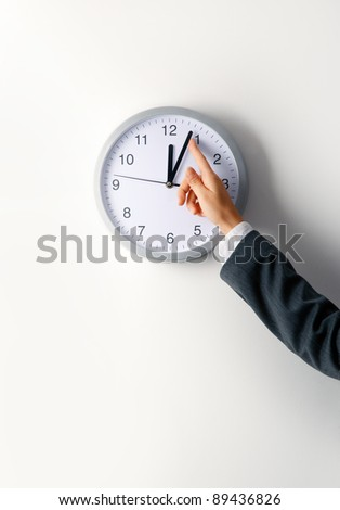 Stopping the time. Woman hand stopping office clock - stock photo