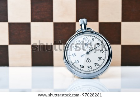 stopwatch and chessboard on a background