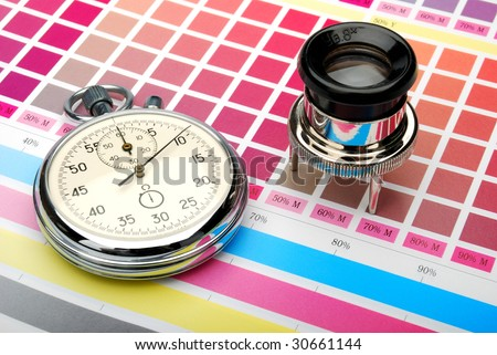 Stopwatch and lupe on a color chart - stock photo