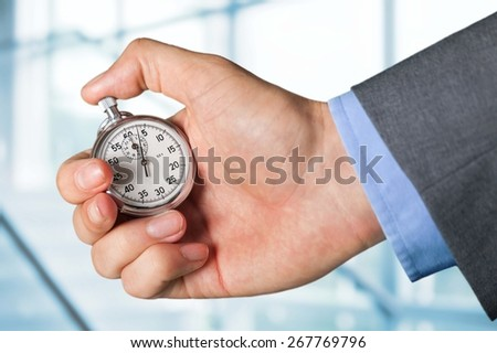 Stopwatch. Holding stop watch - stock photo