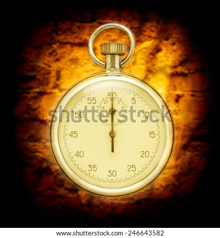 Stopwatch on cracked wall background in yellow toning - stock photo