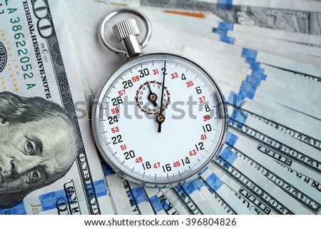 Stopwatch on dollar banknotes, close up. Time is money concept
