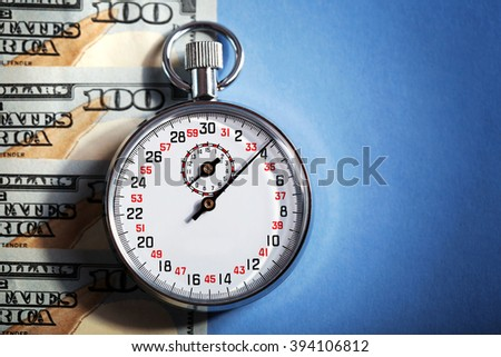 Stopwatch with dollar banknotes on blue background. Time is money concept