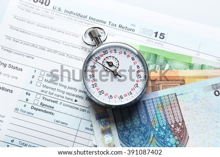 Stopwatch with euro banknotes on form of Individual income tax return - stock photo
