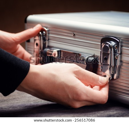 Storage and protection of cash and valuable goods. Business man closes an aluminum briefcase. Money and documents in safe hands of bank employee. - stock photo