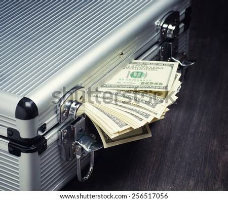Storage and protection of cash and valuable items. Banking concept. Aluminum briefcase full of money and a stack of hundred-dollar bills. Money and documents in safe hands. - stock photo