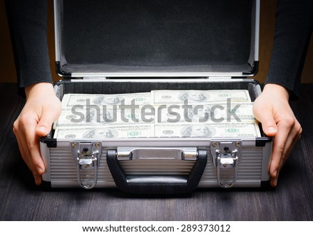 Storage and protection of cash and valuable items. Banking concept. Business man opens an aluminum briefcase full of stacks of hundred dollar bills. Money in safe hands. - stock photo