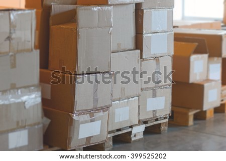 Storage area with stack of battered cardboard boxes - stock photo