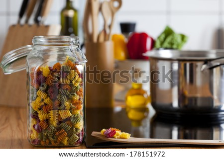 Storage Jar with Colorful Pasta and Cooking Spoon on Worktop with Copy Space at the right Area of the Image - stock photo
