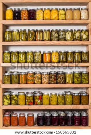 Storage shelves in pantry with homemade canned preserved fruits and vegetables - stock photo