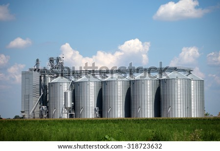 Storage silos on field with blue sky