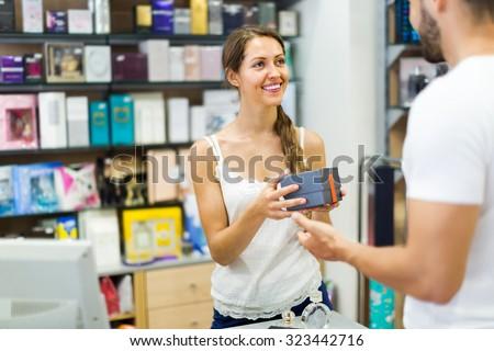 Store clerk serving purchaser at cash desk - stock photo