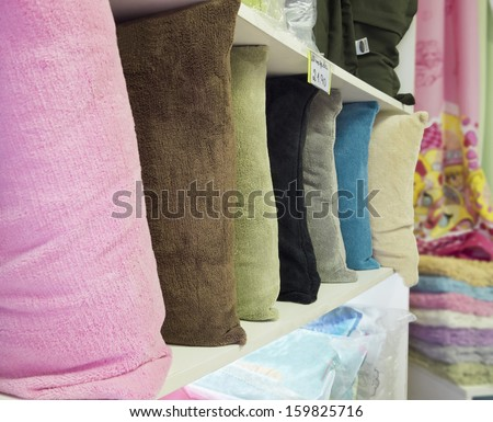 Store decorative items - colorful cushions on the shelf - stock photo
