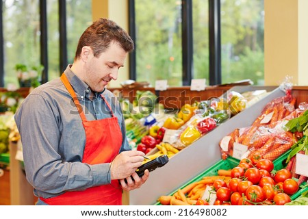 Store manager in supermarket using a mobile data registration terminal - stock photo