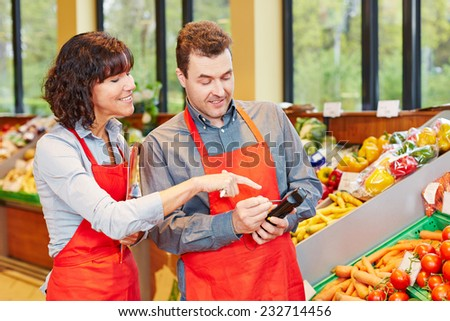 Store manager showing his staff how to use a mobile data registration terminal - stock photo