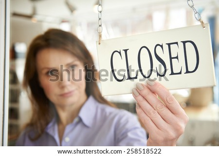 Store Owner Turning Closed Sign In Shop Doorway - stock photo