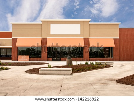 Storefront with awning ready for new tenant at a mixed use retail strip mall - stock photo