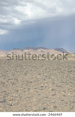 Storm approaches dry river bed - stock photo