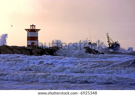 Storm at the north sea with fisherboat going out of the harbor at Scheveningen in Holland at sunset - stock photo