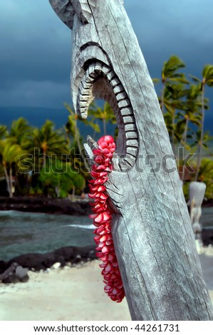 Storm behind tiki makes it look like tiki god is angry. Lei hangs from his gaping mouth at Puuhonua o Honaunau National Historical Park on the Big Island, Hawaii. - stock photo