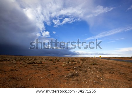 Storm brewing over the red earth of the Australian outback.  Western New South Wales, near Broken Hill.