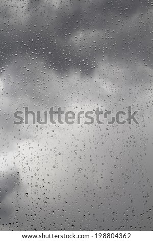 Storm clouds and rain drops on window glass, background - stock photo