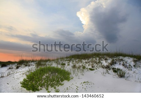 Storm Clouds Approach as the Sun Sets at the Beach - stock photo