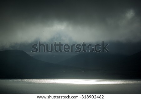 storm clouds approaching over valley and lake in Iceland - stock photo