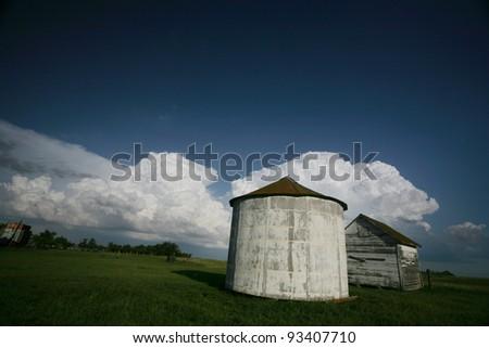 Storm clouds behind old Saskatchewan granaries - stock photo