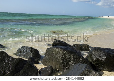 Storm clouds gathering over a tranquil desterted tropical beach with golden sand and a small boat on a calm ocean in a marine background conceptual of a summer vacation - stock photo