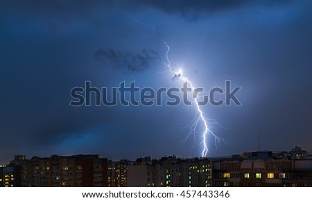 Storm clouds, heavy rain. Thunderstorm and lightning over the night city.
