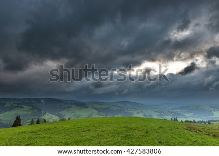 Storm clouds over the mountains and green meadows during sunset - stock photo