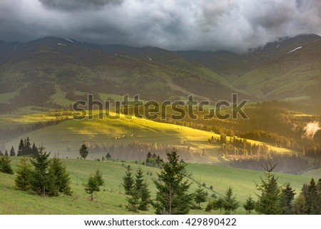 Storm clouds over the mountains and green meadows during sunset. - stock photo
