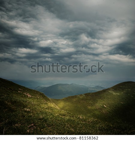 storm clouds over the mountains and small birds in a dark sky - stock photo