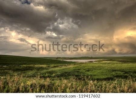 Storm Clouds Saskatchewan sunset over prairie field - stock photo