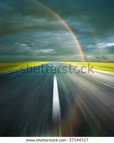 Storm clouds with rainbow and asphalt road with reflection of rainbow - stock photo