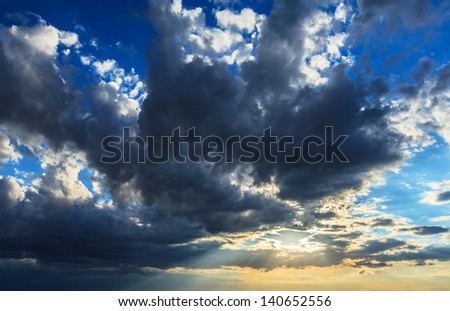 Storm cloudscape with patches of blue sky and sunlight