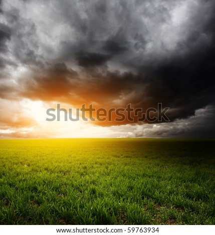 Storm dark clouds and light over field with green grass - stock photo